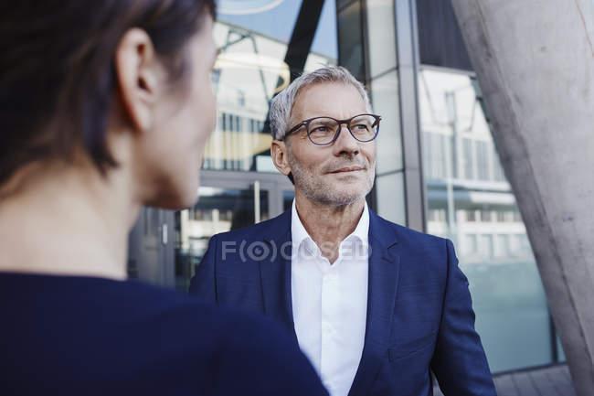 Бізнесмен з бізнес-леді на відкритому повітрі дивиться вбік — стокове фото