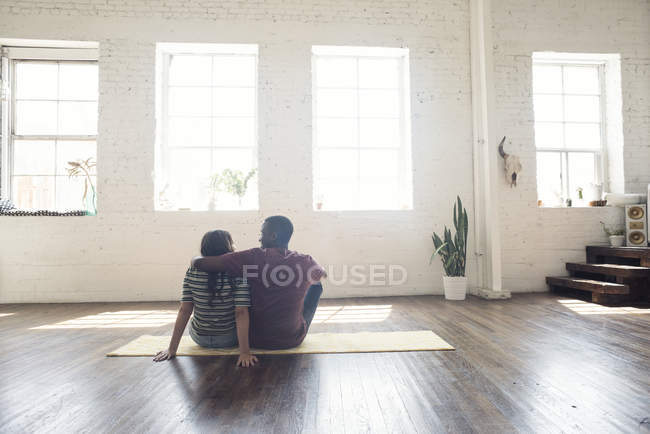 Young couple sitting on carpet in empty loft apartment — Stock Photo