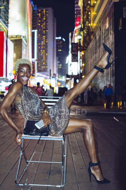 Engraçada mulher americana africana com celular sentado na cadeira na Times Square à noite, NY, EUA — Fotografia de Stock