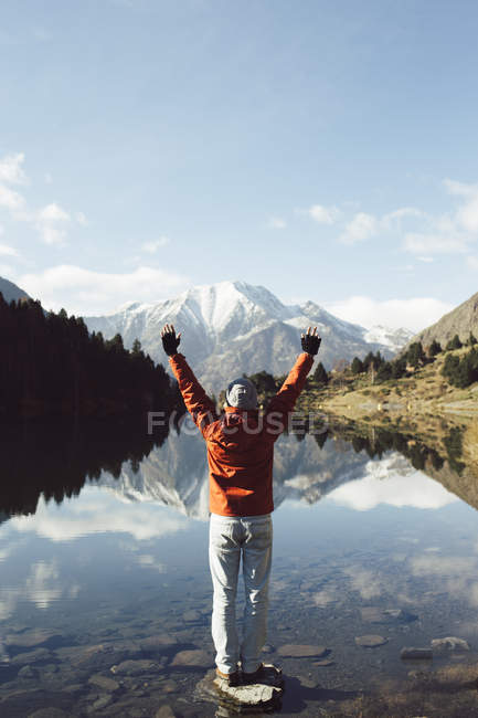 France, Pyrenees, Carlit, hiker raising arms at mountain lake — Stock Photo