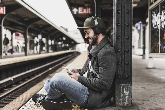 Молодой человек ждет метро на железнодорожной станции платформе и с помощью смартфона — стоковое фото