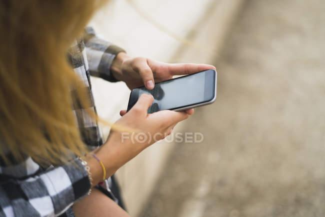 Mani della giovane donna della messaggistica di testo — Foto stock