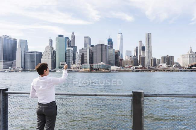Businesswoman taking picture of Manhattan skyline, USA, New York — Stock Photo