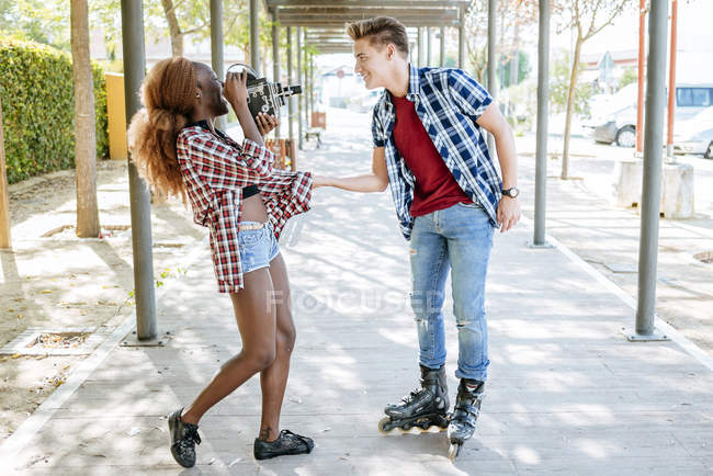 Young woman filming her boyfriend on inline skates with an old-fashioned camera — Stock Photo