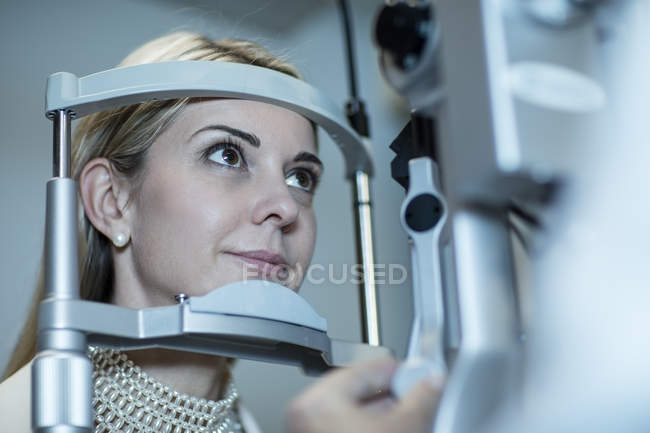 Mature woman doing eye test at the optometrist in medical clinic — Stock Photo