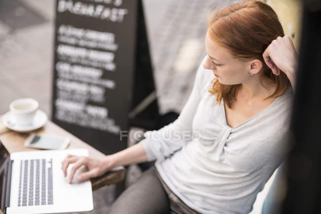Ebony дівчина кавказька жінка, використовуючи ноутбук у кафе — стокове фото