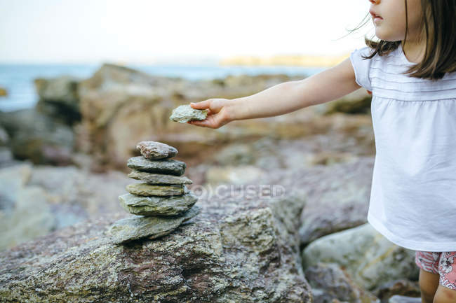 Girl stacking stones at rocky coast — Stock Photo