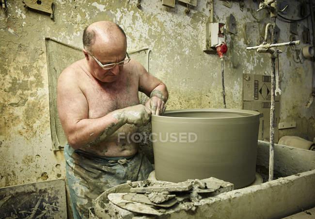Поттер в мастерской работает над большой терракотовой вазой — стоковое фото