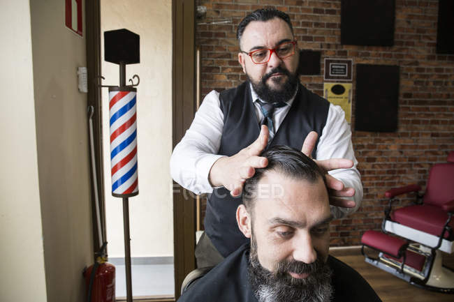 Barber checking the haircut of a man in barbershop saloon — Stock Photo