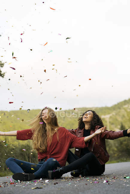 Two best friends sitting on country road and throwing confetti in air — Stock Photo