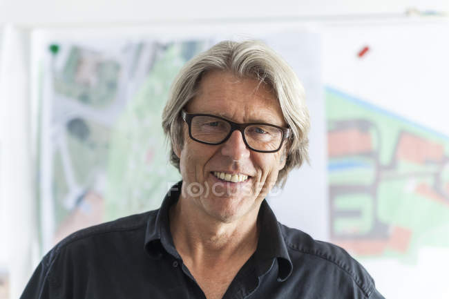 Portrait of smiling mature man in office — Stock Photo