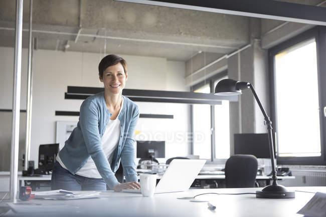 Портрет впевнено бізнес-леді з ноутбуком стоячи в офісі — стокове фото