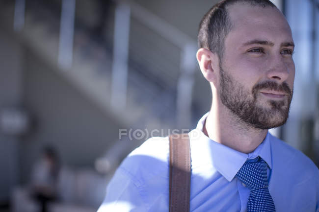 Young businessman in office building, looking aside, portrait — Stock Photo