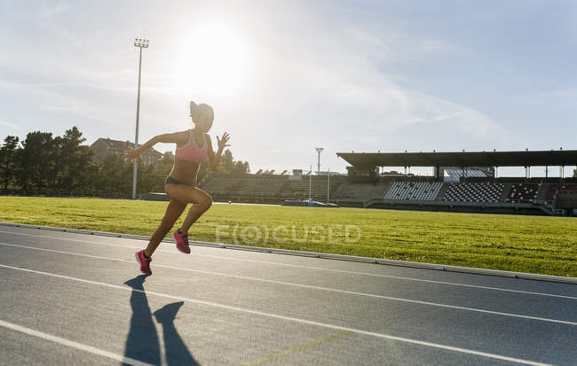 Side view of sprinter woman running in a race track — Stock Photo