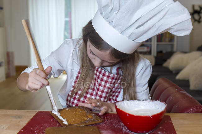Girl preparing gingerbread house at home — Stock Photo