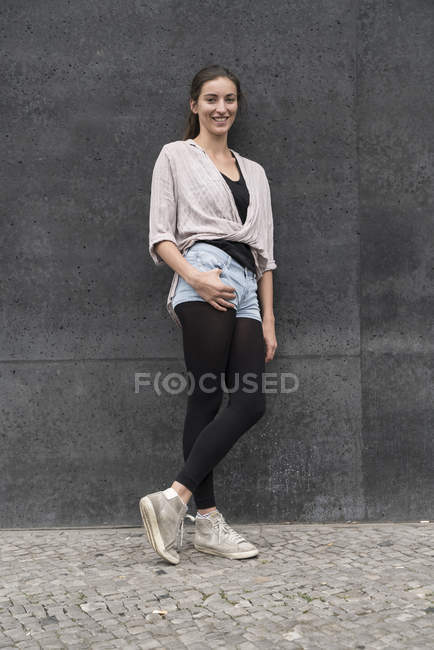 Ritratto di giovane donna sorridente appoggiata al muro — Foto stock