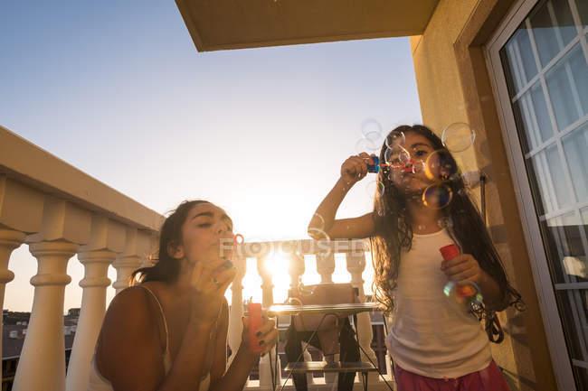 Adolescente e la sua sorellina che soffia bolle di sapone sul balcone — Foto stock