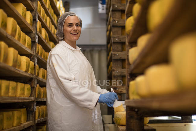 Cheese factory worker applying wax on cheese — Stock Photo