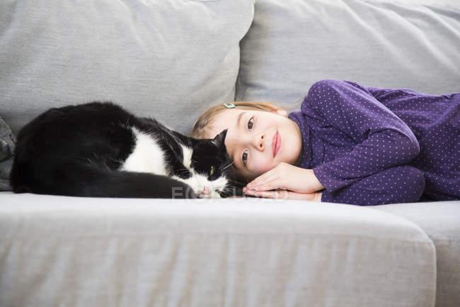 Retrato de niña acostada en un sofá con gato - foto de stock
