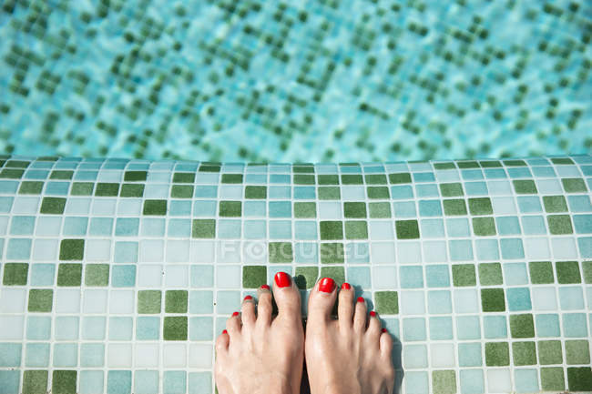 Woman's feet at poolside — Stock Photo
