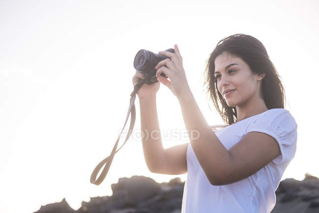 Young woman taking pictures on beach — Stock Photo