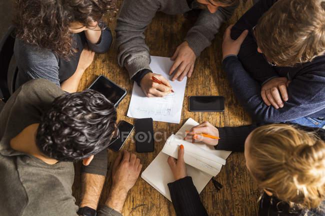 Colaboradores trabajando en un proyecto sobre mesa de madera - foto de stock