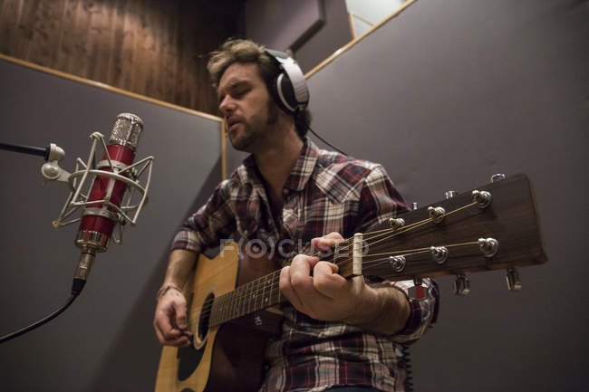 Man playing guitar in a recording studio during a musical recording — Stock Photo