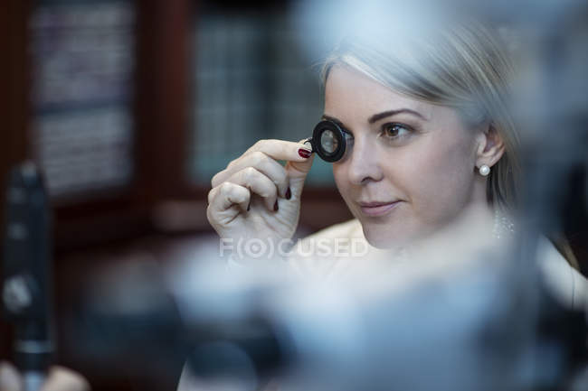 Patient at optometrist trying different lenses in medical clinic — Stock Photo