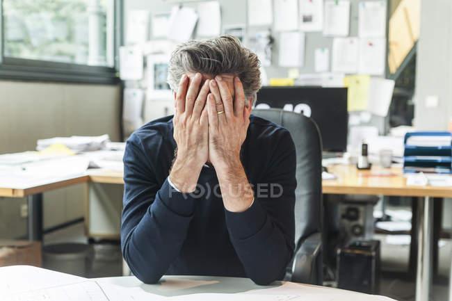 Hombre maduro sentado en la oficina con la cabeza en las manos - foto de stock