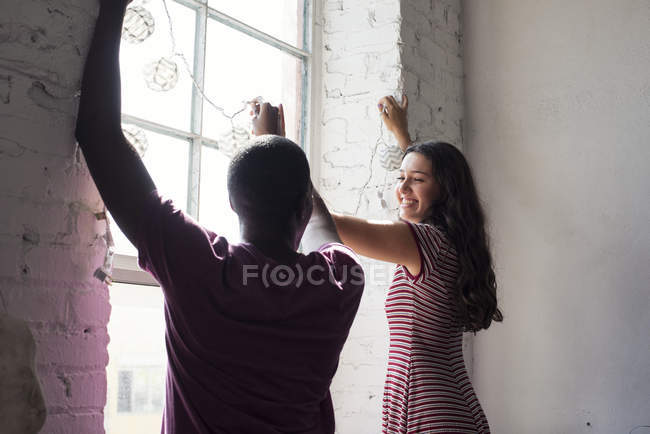 Young couple decorating window with fairylights — Stock Photo