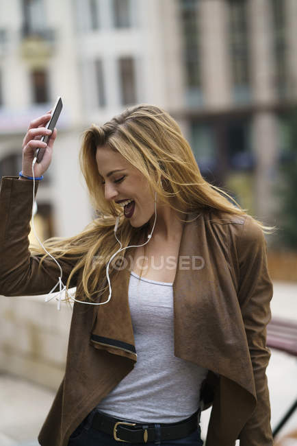 Happy young woman listening music with earphones and smartphone — Stock Photo