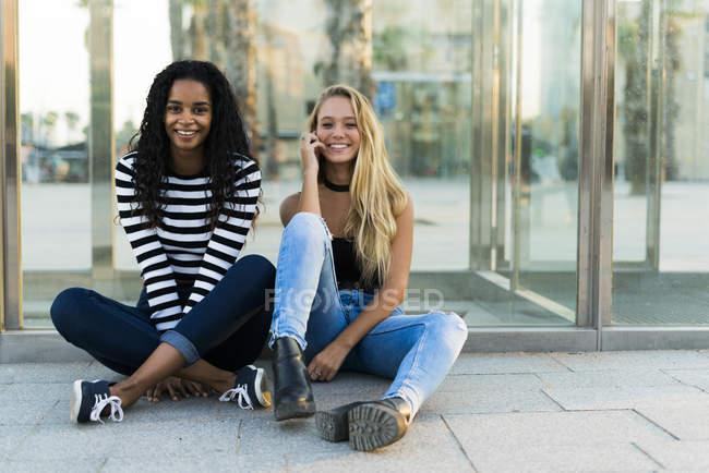 Два щасливі молоді жінки сидять в скляну стіну з мобільного телефону — стокове фото