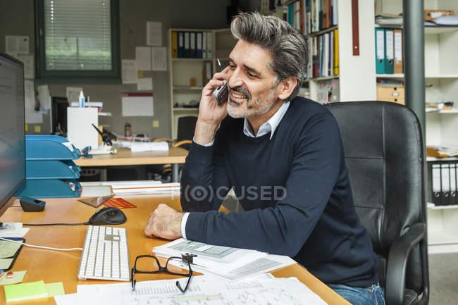 Arquiteto sentado na mesa e falando ao telefone — Fotografia de Stock