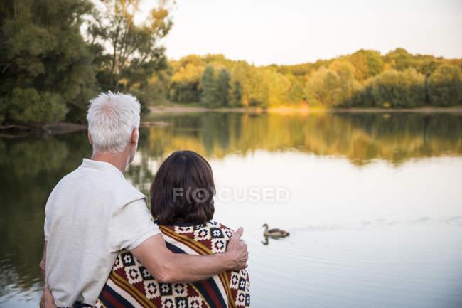 Casal sênior em um lago olhando para pato — Fotografia de Stock