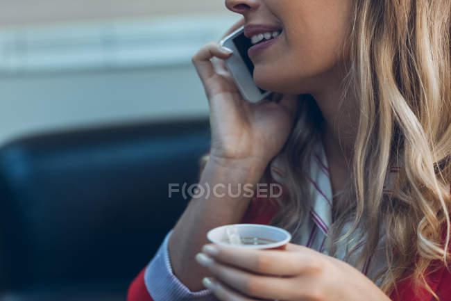 Mulher sorridente com café para viagem, falando no celular, close-up — Fotografia de Stock