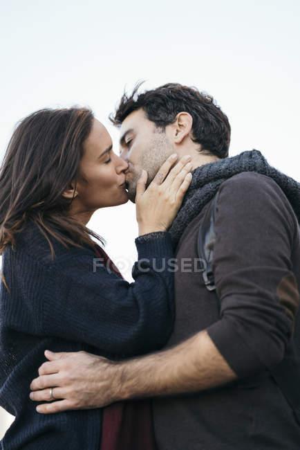 Ласкавим пара поцілунки у присутності небо — стокове фото