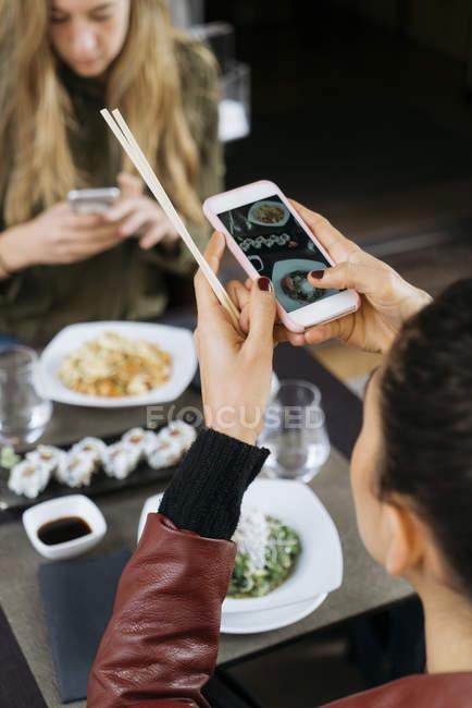Женщина принимая фотография суши в ресторане с другом на фоне — стоковое фото