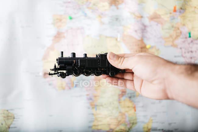 Uomo che tiene locomotiva giocattolo davanti alla mappa del mondo — Foto stock
