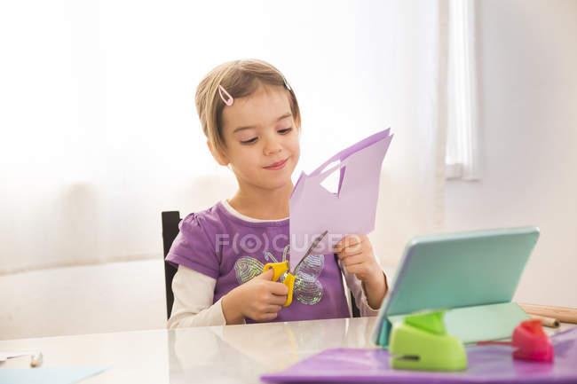 Petite fille bricolant à la maison, coupant du papier avec des instructions en ligne — Photo de stock