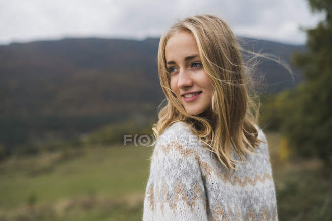 Smiling young woman wearing pullover standing in nature — Stock Photo
