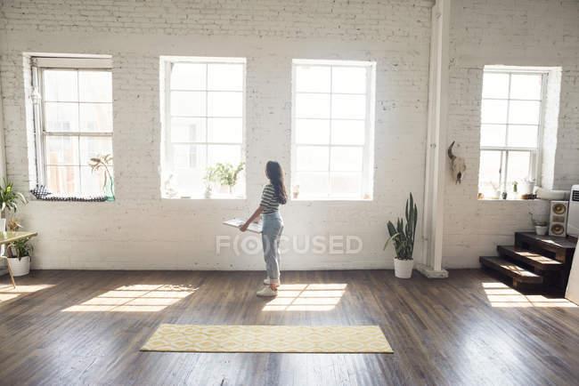 Молодая женщина, стоя в чердак Холдинг рамку рисунка — стоковое фото