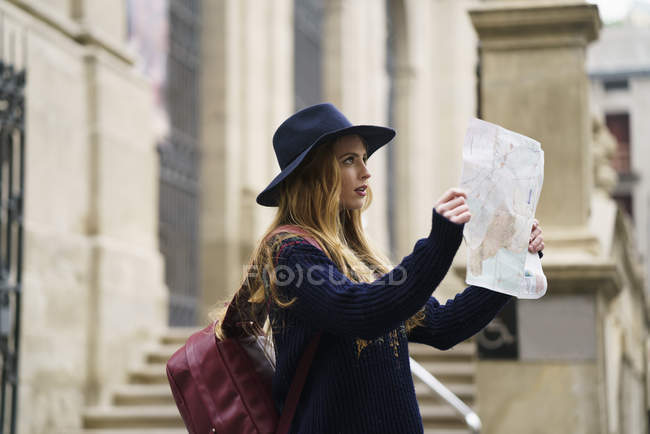Turista con zaino e mappa della città guardando qualcosa — Foto stock