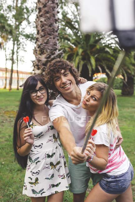 Glückliche Freunde im Park unter einem Selfie mit Selfie-stick — Stockfoto