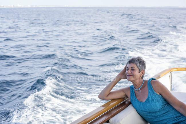 Mulher sorridente desfrutando em uma viagem de barco — Fotografia de Stock