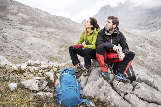 Spain, Picos de Europa, mountaineers resting on rock — Stock Photo