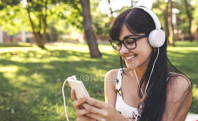 Felice giovane donna nel parco ascoltando musica — Foto stock