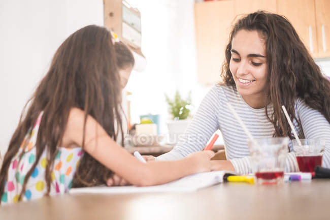 Teenage girl and her little sister drawing together — Stock Photo