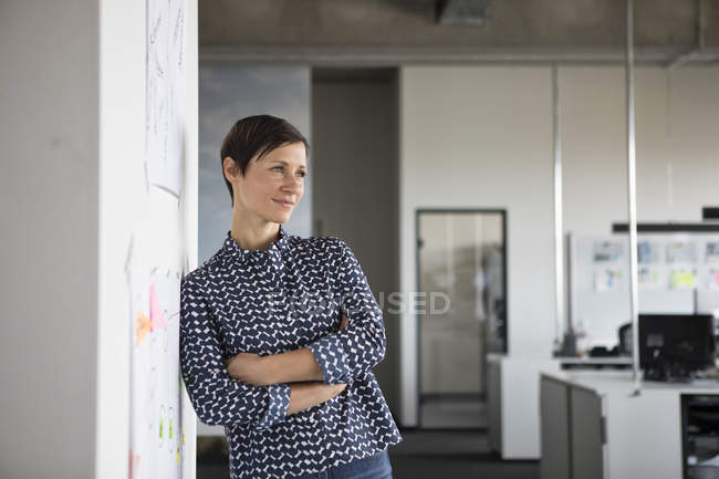 Бізнес-леді стоячи в офісі з руками, перетнув і мислення — стокове фото
