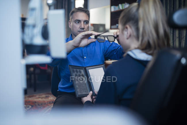 Optometrist doing eye test with girl in medical clinic — Stock Photo