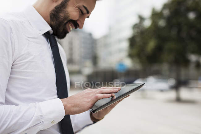 Smiling businessman using tablet on street — Stock Photo